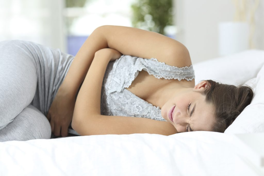 Girl suffering menstrual pains lying on the bed at home
